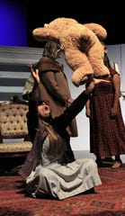 "Fairy Mae (Emilee Garcia) joyfully tosses a stuffed bear brought by Mrs. Savage (Avery French, in coat) in Wylie High's ""The Curious Savage."""