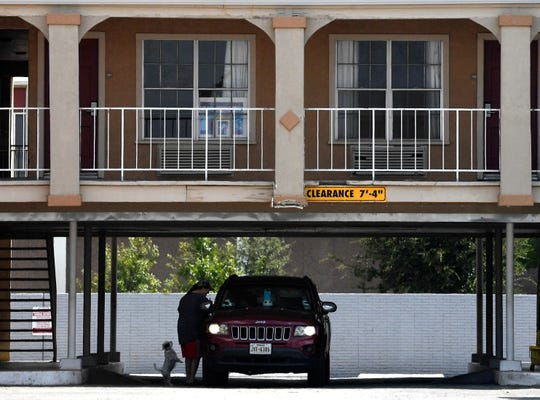 A dog stands on its hind legs as a woman speaks to a driver at Civic Plaza Hotel in downtown Abilene on Tuesday.