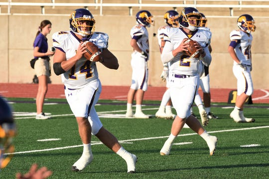 Wylie quarterbacks Jaxon Hansen (14) and Balin Valentine (2) drop back to pass during pregame warmups before facing Stephenville last week. The two juniors have split time under center this season.