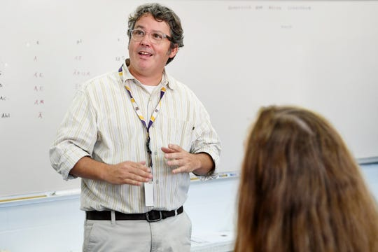 Roberson Latin teacher Chris Semper talks with his students during a lesson September 12, 2019.
