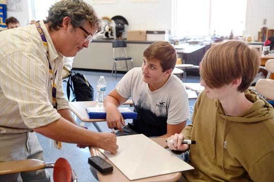Chris Semper helps Roberson students Sean Brigman, center, and Christian Beaver compose a sentence in Latin September 12, 2019.