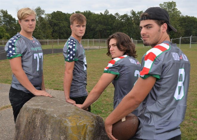 Pennfield captains Jack Boyd, Cody Hultink, Seth Clothier and Ryne Petersen show off the uniforms Pennfield will be wearing on Military Appreciation Night - featuring the words 'Honor' and 'Valor' on the back.