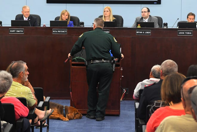 Brevard County Sheriff Wayne Ivey, accompanied by Brevard County Sheriff's Office dog Junny, addressed Brevard County commissioners on Tuesday. Ivey and members of his department were at the meeting to accept a resolution honoring the BCSO's efforts related to Hurricane Dorian.