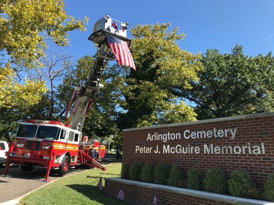 A Camden Fire Department ladder truck flies an American flag outside Arlington Cemetery in Pennsauken. A ceremony there honored two city firefighters killed in the line of duty in 1914 and 1922.