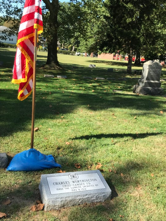 A flag and new headstone mark the final resting place for Chief Charles Worthington, a Camden firefighter killed in the line of duty in 1914.