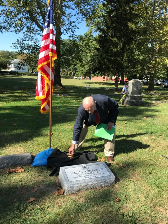Lee Ryan, the Camden Fire Dept. historian, adjusts a cloth at the grave of Chief Charles Worthington.