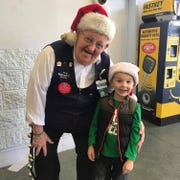 "Bob ""Mr. Bob"" Coates smiling with a shopper's son during the Christmas season."