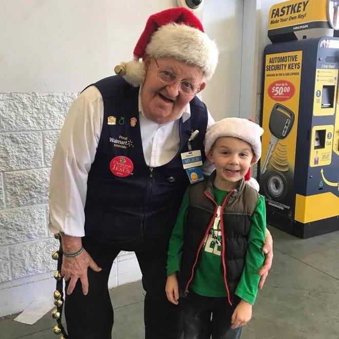 "Bob ""Mr. Bob"" Coates smiling with a shopper's son during the Christmas season."