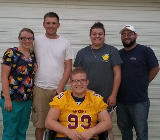 Jennifer Rabbit, Jon Munson, Quinton Munson, Cyndy Phillips and Ryan Phillips of Ankeny comprise Quinton's family and pose together with him as he wears his Ankeny Hawks jersey.