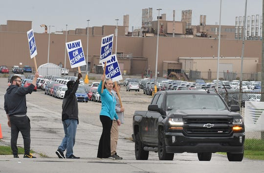 Debbie Gibson, in blue, and other UAW workers react as pickup truck driver honks the horn in support of the strikers on the south side of the GM Lake Orion Assembly plant in Lake Orion, Michigan on September 16, 2019.