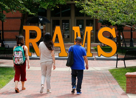 In this June 20, 2019, file photo students walk around a RAMS sign at Virginia Commonwealth University in Richmond, Va. Thinking of refinancing your student loans? Make sure you understand the pros and cons before deciding, and know how to make yourself look good to lenders.
