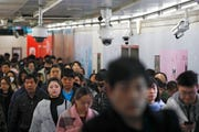 In this Feb. 26, 2019, file photo commuters walk by surveillance cameras installed at a walkway in between two subway stations in Beijing.