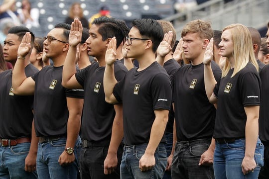 FILE - In this June 4, 2017, file photo. nNew Army recruits take part in a swearing in ceremony before a baseball game between the San Diego Padres and the Colorado Rockies in San Diego. A year after failing to meet its enlistment goal for the first time in 13 years, the U.S. Army is now on track to meet a lower 2019 target after revamping its recruitment effort.