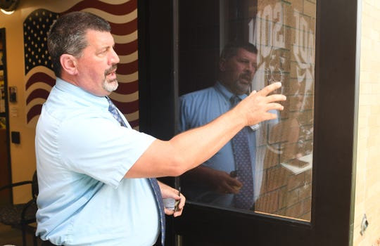 Addison School's Superintendent Steve Guerra looks at the 3M window film  installed over 192 windows to make them shatterproof on the Addison Schools' campus.  A $48,000 grant from the Michigan State Police paid for the window treatments.