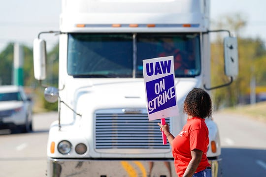 A striking plant worker blocks the passage of a truck outside the General Motor assembly plant in Bowling Green, Ky, Monday, Sept. 16, 2019.