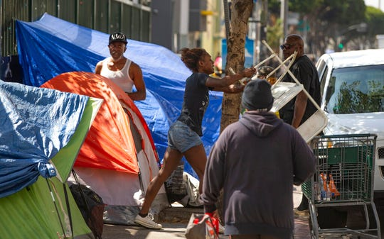 A homeless woman throws a plastic chair in the air downtown Los Angeles Tuesday, Sept. 17, 2019. The White House released a report on homelessness on Monday that described the issue largely as a result of over-regulation of the housing market, exacerbated by lax policing and an abundance of homeless shelters in Democratic-led cities.