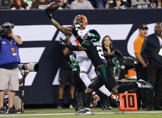 Cleveland Browns' Odell Beckham (13) catches a pass in front of New York Jets' Nate Hairston (21) during the first half Monday.