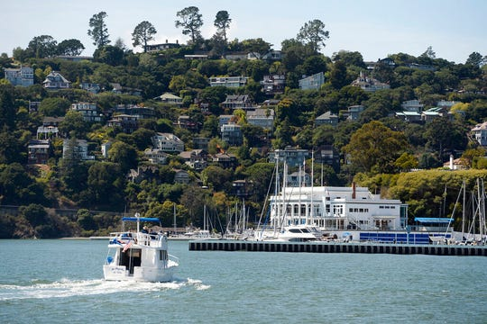 A boat motors toward the Corinthian Yacht Club in Tiburon, Calif., Monday, Sept. 16, 2019, with the town of Belvedere on the hill in the background. A Belvedere father was arrested on manslaughter charges after his 11-year-old son was thrown overboard a boat in the San Francisco Bay and killed after being struck by the vessel, police said.