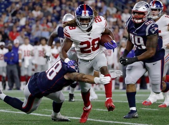 New England Patriots linebacker Calvin Munson (48) tackles New York Giants running back Paul Perkins (28) in the first half of an NFL preseason football game, Thursday, Aug. 29, 2019, in Foxborough, Mass. (AP Photo/Elise Amendola)