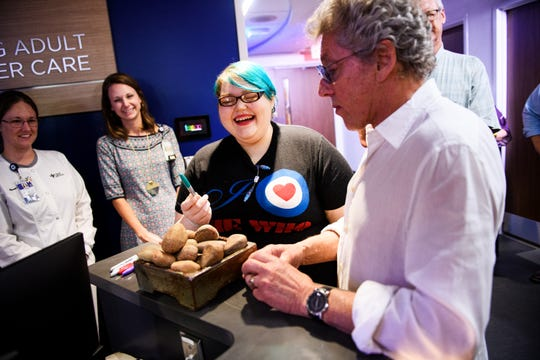 Roger Daltrey, lead singer of The Who, signs a commemorative rock with patient Kelsey Morris at the new Hawkins Family Adolescent and Young Adult Cancer Center at St. Francis Downtown Tuesday, Sept. 17, 2019.