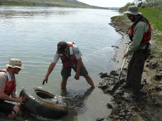 Volunteers help a BLM officer remove a tire from the Missouri River