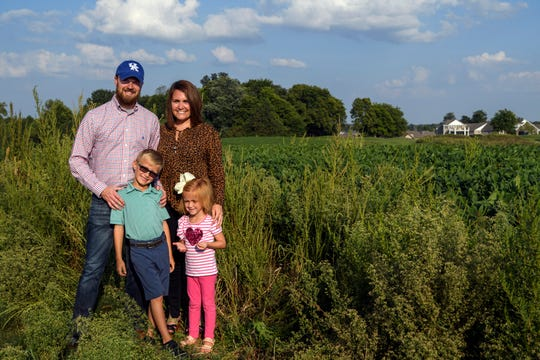 Patrick and Jessica Beaven and their children -- Hudson, 7, and Cate, 4 -- stand in front of an empty field along Green River Road, which will be developed into a senior living complex called the Homeplace of Henderson. Jessica will be the executive director of the facility, while Patrick works as the business manager.