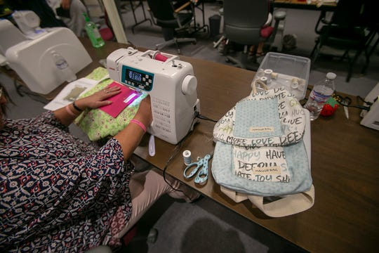 """Resident Kimberly Kingsbury uses a sewing machine to make a Maggie Bag, Tuesday, Aug. 27, 2019, at the Maggie Bags store and warehouse in Martinsville, Ind. Maggie Bags is part of the Magdalene House, the only homeless women's shelter in Martinsville. """"You can work at the addition part, but if they don't have life-skills, they are not going to make it,"""" Julie VanWinkle said."""