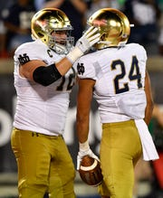 Notre Dame Fighting Irish offensive lineman Robert Hainsey (72) celebrates with tight end Tommy Tremble (24) after scoring a touchdown agains the Louisville Cardinals during the second half at Cardinal Stadium. Notre Dame defeated Louisville 35-17.