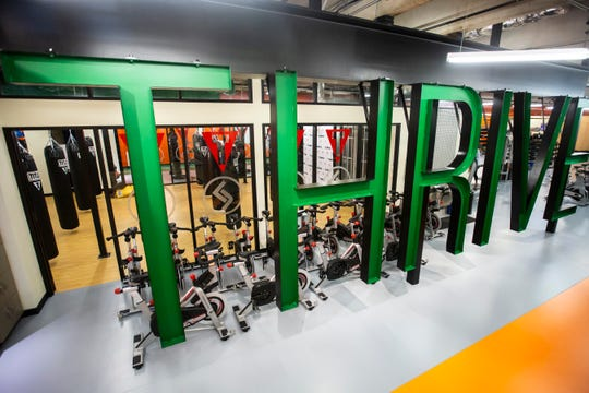 "Large block letters made out of metal spell out ""THRIVE"" adjacent to the staircase leading into the gym, Tuesday, Sept. 17, 2019, at Thrive Gym and TITLE Boxing Club in Coralville, Iowa."