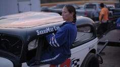 """Sarah Canning climbs into her Classic Division race car in pit lane at Volunteer Speedway in Bulls Gap, Tenn. Canning, who also is a welder, says women who work in male-dominated fields have to prove themselves. """"You got to work twice as hard, but it breaks even in the end,"""" she said."""