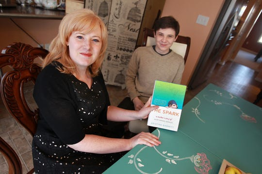 """In this Indianapolis Star file photo from April 2013, Jacob Barnett, 14, right, smiles as his mother Kristine Barnett shows her new book, at their Westfield home. The boy genius, who has autism, loves the theoretical study of physics, as well as math, including trigonometry.  His mother, has written the book, """"The Spark:  A Mother's Story of Nurturing Genius."""""""