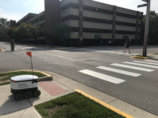 A Starship Delivery Robot waits to cross the intersection of Third Street and Waldron Street on Purdue's campus.