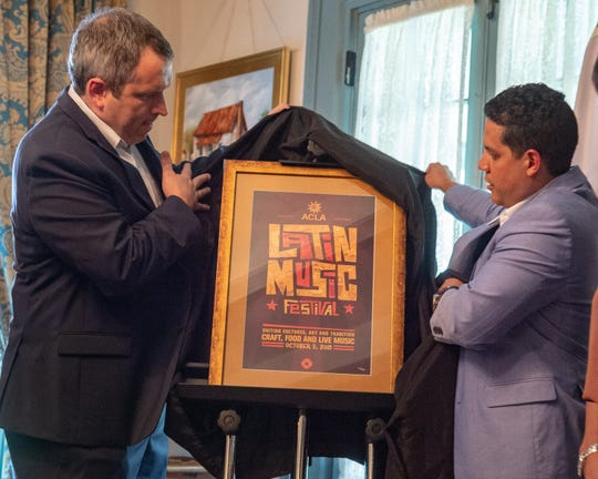 Festival International de Louisiane collaborates with Latin Music Festival for 2019. Scott Feehan and Manuel Pena unveil the 2019 Festival pin and poster. Tuesday, Sept. 17, 2019.