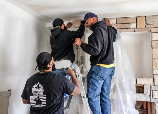 Michael McKissic, right, works directly with Corey Morris, left, and Tommie Miller on finishing a wall and ceiling at a house he is repairing as part of project for his foundation, Mikey 23 Tuesday, Sept. 17, 2019.