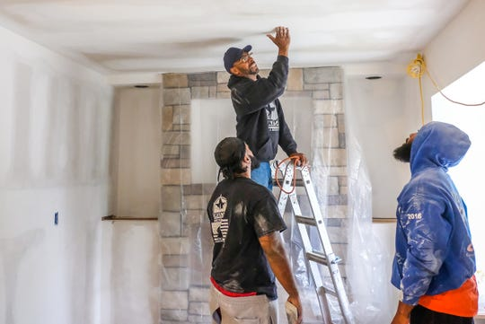 Michael McKissic shows Corey Morris, left, and Rico Stewart an area on the ceiling that needs to be sanded a little more Tuesday, Sept. 17, 2019.