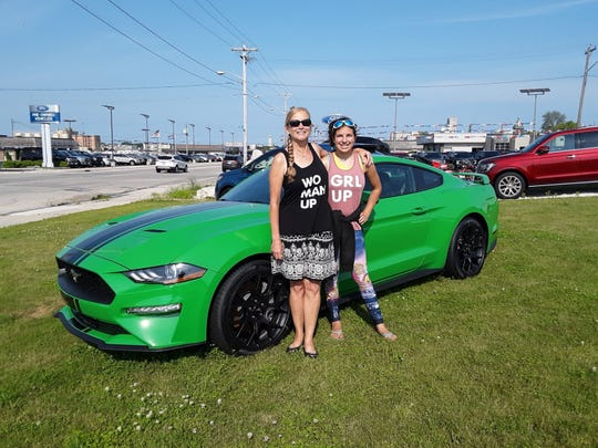 """Big Sister Aimee Augustine (left) and Little Sister Sabrina created their own Big Brothers Big Sisters activity titled """"Muscle Car Mania,"""" where they test-drove some of Sabrina's dream cars."""