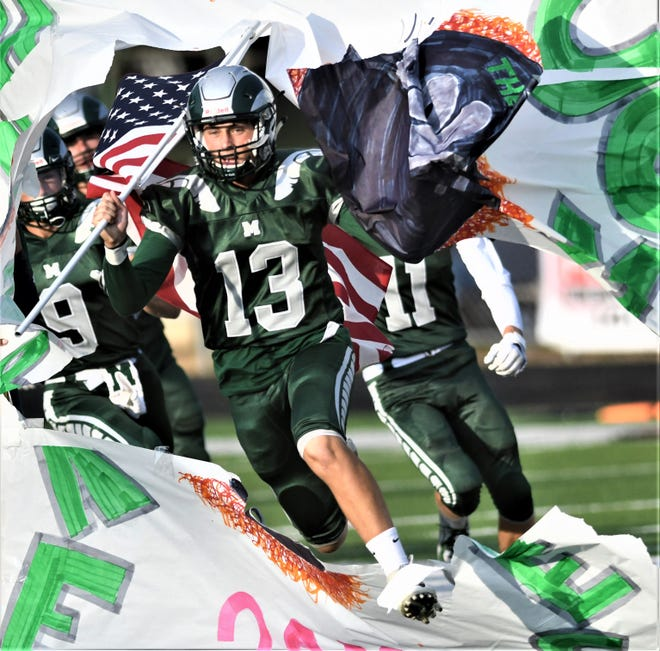 Madison's Kaden Mullins busts through the poster carrying the American Flag during the Rams' Week 1 game against Shelby.