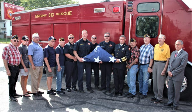 Members of the Marion Township Fire Department, the Wall That Heals Honor Guard, and Marion Township Trustee Larry Ballinger, far right, display the flag Marion Community Credit Union donated to the department on Tuesday. The Marion Township Fire Department flew the flag, which is 40 feet long when unfurled, across the roadway when the Wall That Heals traveling memorial motorcade entered Marion in July.