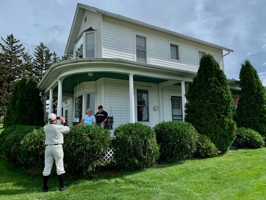 """Craig Purcell, a guide who gives tours of the 1906 farmhouse used in the """"Field of Dreams"""" movie, snaps a photo of a couple on the home's porch swing, which was featured in the film."""