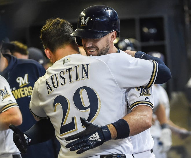 Brewers second baseman Travis Shaw  receives a hug from first baseman Tyler Austin (29) after hitting a pinch hit solo home run in the fifth inning.