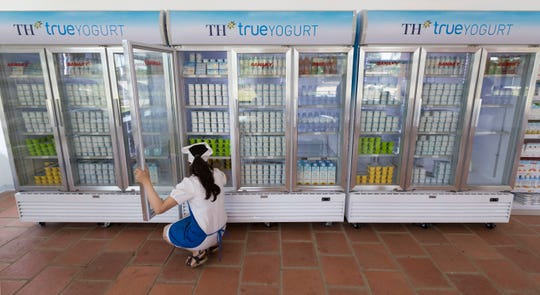 A worker takes care of inventory at a TH Truemart factory store in Nghia Son, Vietnam.