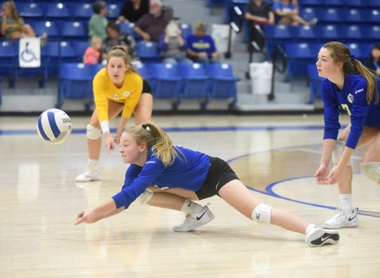 Mountain Home's McKenzie Tolbert dives to receive a serve as teammates Cate Jackson and Chloe Lydon look on during the Junior Lady Bombers' victory over Jonesboro MacArthur.
