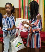 Breanna Bennett, left, and her twin sister Brooke Bennett hand out bags of hygiene and feminine hygiene products to girls at the New Beginnings Education Center in Montgomery, Ala., on Tuesday September 17, 2019. The twins started the WIT (Women in Training) organization to distribute feminine hygiene products to low income girls.