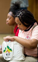 Young girls check out bags of hygiene and feminine hygiene products given to girls at the New Beginnings Education Center in Montgomery, Ala., on Tuesday September 17, 2019.