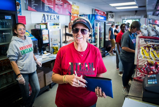 Jennifer Cooper empties registers in a concession stand at Scheumman Stadium.