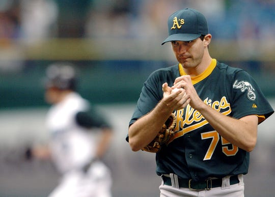 Oakland Athletics starter Barry Zito rubs up a new ball as Tampa Bay Devil Rays' Jorge Cantu circles the bases after a solo home run off him during the second inning on Sept. 10, 2006 in St. Petersburg, Fla.