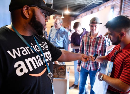 Sean Hairston gives out information to job seekers at Amazon's highly publicized Career Day at the Cannery Tuesday, Sept. 17, 2019, in Nashville, Tenn.