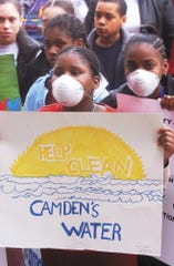 Camden Residents rally for clean water at the State house in Trenton. left to right: wearing masks and holding protest sign are Zamora Thomas,12, and Tanay Oliver,15, both Leap Academy students. Photo by Al Schell (Submit Date: Thursday, March 7, 2002)