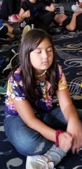 Rania Hakimi, a fourth grader at Woodmont Elementary School in Montville, practices meditation in class.