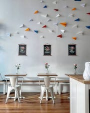 Paper planes speckle the wall of the coffee shop.